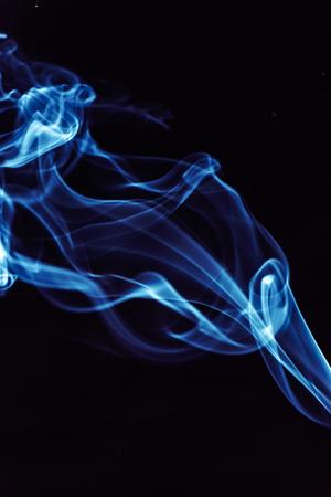 fuming: Blue smoke on a black background