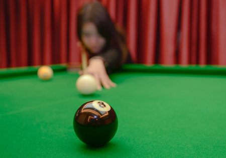 Young girl playing billiard. Spending free time on gambling Stock Photo