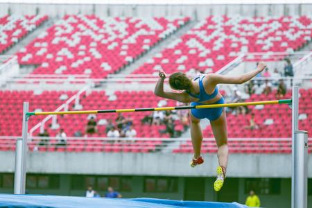 Athlete performing a high jump at stadium, china
