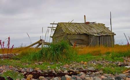 Old abandoned fishermans cabin at White Sea coast, northern Russia photo