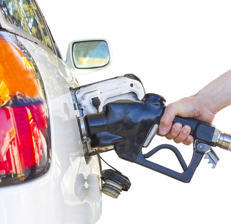 Hand holding a nozzle while fueling white car.  Focus on the nozzle. photo
