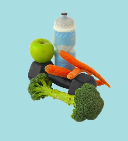 Dumbells made of broccoli with water bottle, carrots and green apple photo