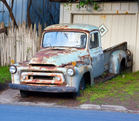 junk yard: Rusted blue vintage pickup truck.