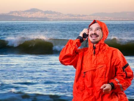 kayaker: Man in storm cog talking on marine radio.