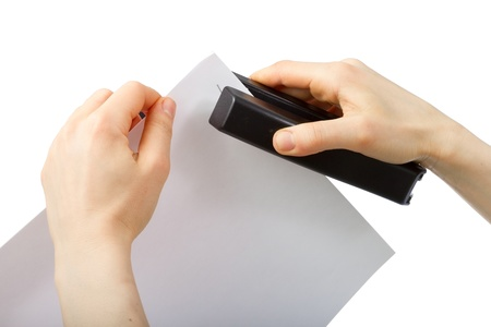 office stapler: Hands holding stepler and paper isolated on white background