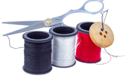 Set of thread spools, needle, button and scissors isolated on white background