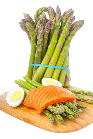 Fresh asparagus, boiled egg and raw salmon fillet on cutting board isolated on white background  photo