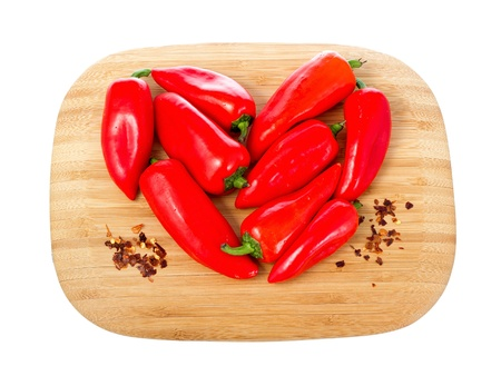 Heart shape made of red hot peppers on wooden cutting board isolated on white background  photo