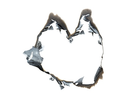 Heart shaped burned hole in paper. isolated white space inside the frame. photo