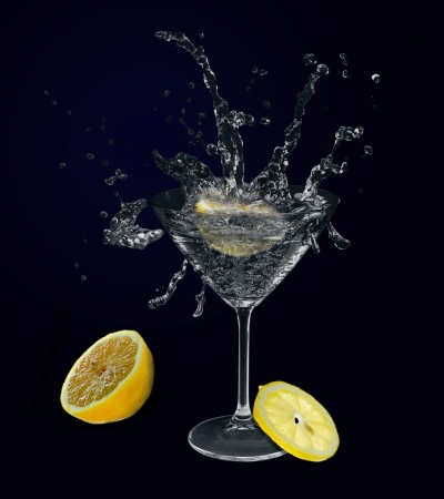 Lemon splashing in martini glass on dark background. photo