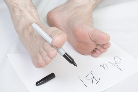 Caucasian male writing alphabet using  foot. photo