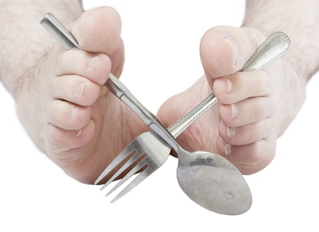 bad manners: Caucasian male feet holding silverware. Stock Photo