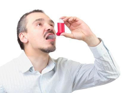 Caucasian male inhaling aerosol spray dedication isolated on white background.