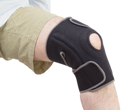 knee bend: Caucasian adult putting on neoprene knee brace isolated on white background. Stock Photo