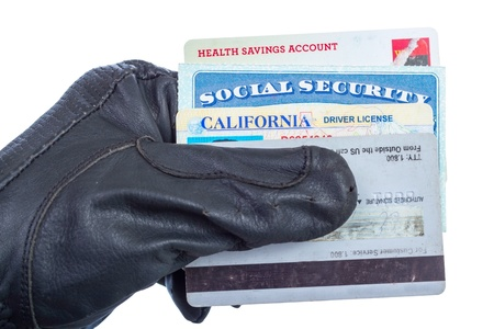 Identification documents  social security, driver license and credit cards  in hand of thief, isolated on white  Imagens