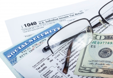 filing documents: American federal tax form 1040 with money and social security card isolated on white  Stock Photo