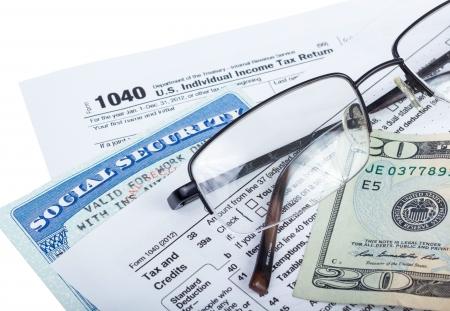 seguridad social: Americana formulario de impuestos federal 1040 con dinero y tarjeta de seguro social aislado en blanco Foto de archivo
