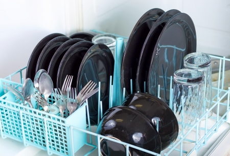 Dishwasher rack loaded with clean plates, glasses and silverware.