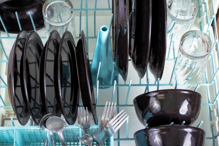 black appliances: Dishwasher rack loaded with clean plates, glasses and silverware.