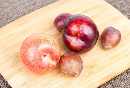 Pluot, plum and prunes on wood cutting board 版權商用圖片