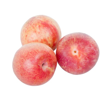 Ripe pink pluots isolated on white background .