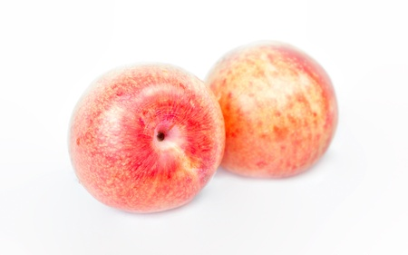 Ripe pink pluots on white background .