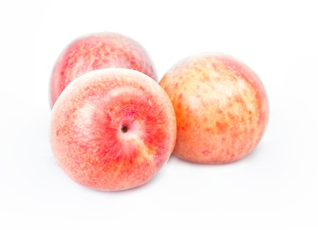 Ripe pink pluots on white background . photo