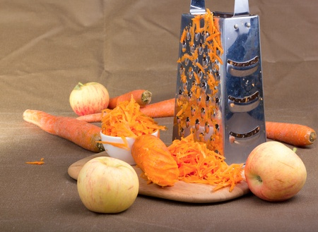 shredding: Stainless still grater and grated carrot on warm broun background. Stock Photo