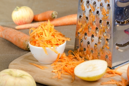 Stainless still grater and grated carrot on warm broun background. Reklamní fotografie