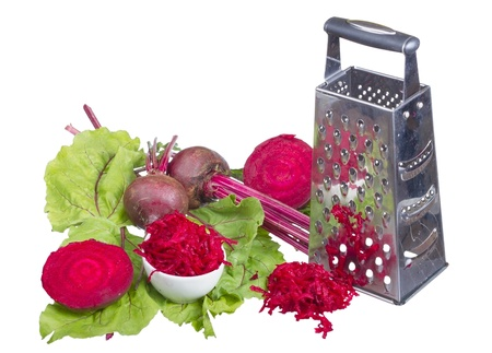 Stainless steel grater and grated beet isolated on white background. photo