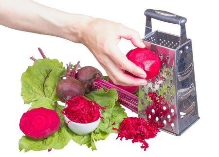 Stainless steel grater and grated beet isolated on white background.