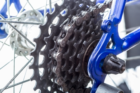 lubrication: Dusted bicycle rear sprockets with chain on, close up.