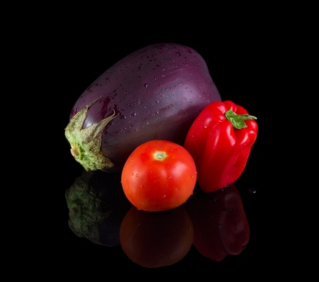 Eggplant, tomato and bell papper isolated on black background with reflection. photo