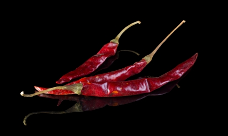 Dried Arbol chilli pepper isolated on black background with reflection. photo