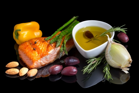 king salmon: Mediterranean omega-3 diet. Fish steak, olives, nuts and herbs isolated on black background with reflection. Stock Photo