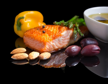 Mediterranean omega-3 diet. Fish steak, olives, nuts and herbs isolated on black background with reflection. Standard-Bild