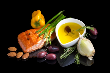 Mediterranean omega-3 diet. Fish steak, olives, nuts and herbs isolated on black background with reflection. photo