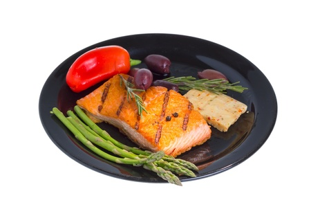 king salmon: Grilled salmon steak on plate served with olives, asparagus and bell pepper isolated on white background.
