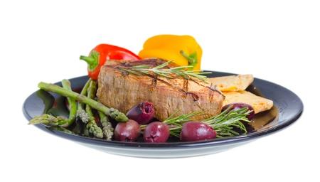 プレートに牛肉のグリル オリーブ、ローズマリー、高齢者チーズ、白い背景で隔離の野菜を添えてください。 写真素材