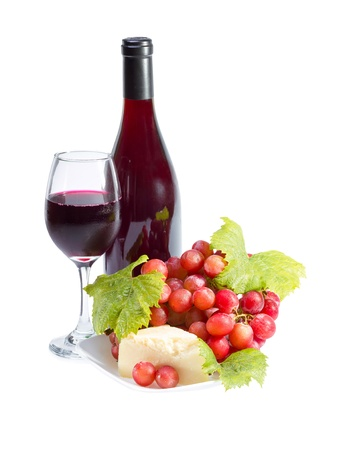 Full glass of red wine, bottle, cheese and grapes with leaves isolated on white background. photo