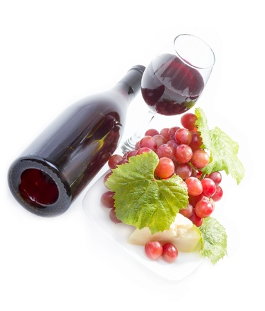 Full glass of red wine, bottle, cheese and grapes with leaves on white background. photo