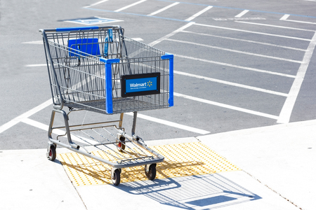 SACRAMENTO, USA - SEPTEMBER 13: Walmart shopping cart on September 13, 2013 in Sacramento, California. Walmart is an American multinational retail corporation that runs chains of large discount department stores
