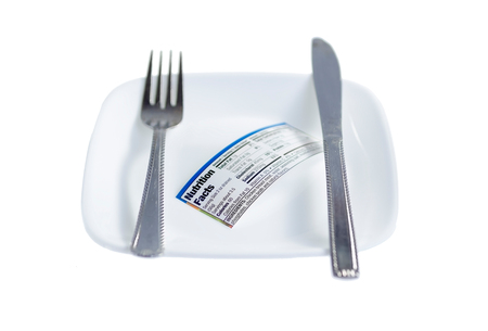 nutritional: Knife and fork laid side by side with nutritional facts label on plate isolated on white background. Selective shalow focus on the label.