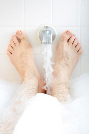 Male feet soaking in the bathtub with faucet runnng water. photo