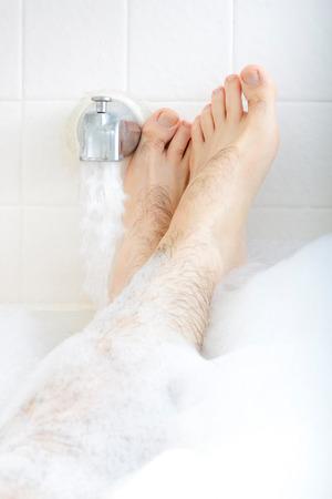 男性の足は、水道水の稼働と湯船に浸漬します。 写真素材