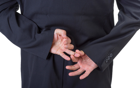 Man removing marriage ring from his finger behind his back isolated on white . photo