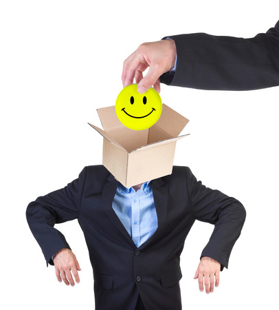 indoctrinate: Hand putting smiley into mans head represented as an open empty card box isolated on white.