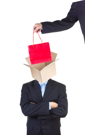 indoctrinate: Hand putting red shopping bag into mans head represented as an open empty cardbox isolated on white.