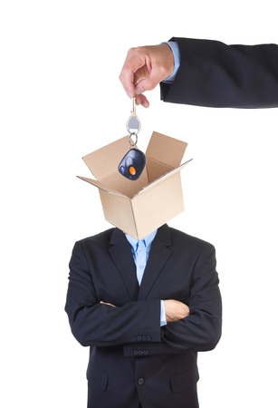 indoctrinate: Hand putting cars key into mans head represented as an open empty cardbox isolated on white . Stock Photo