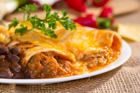 mexican food: Southwest beef enchilada with sourcream and black beans.